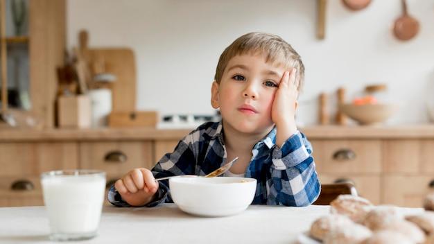 Vista frontal menino bonitinho tomando café da manhã Foto Premium