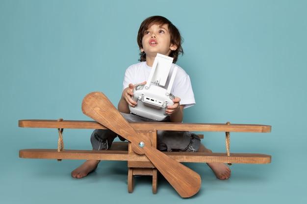 Vista frontal menino bonito adorável segurando o controle remoto com avião de madeira em cima da mesa azul