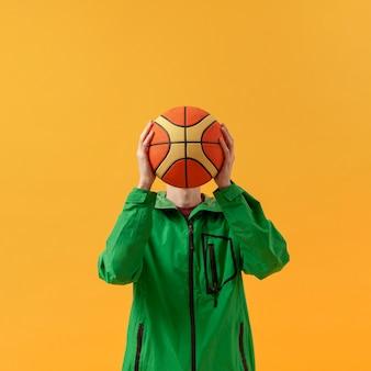 Vista frontal, menino brincando com bola de basquete
