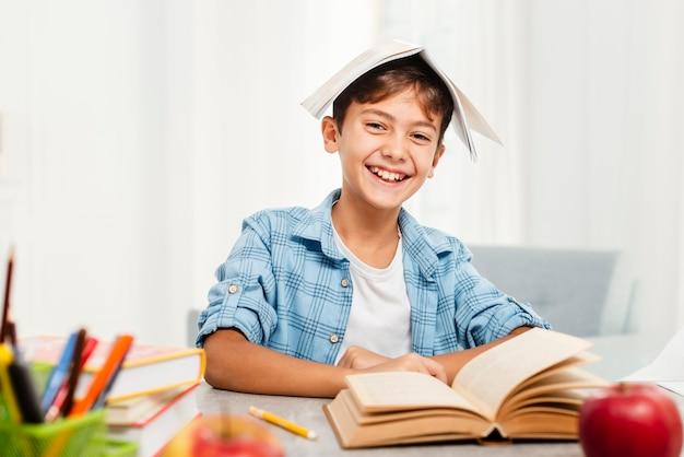 Vista frontal, menino brincando com livros