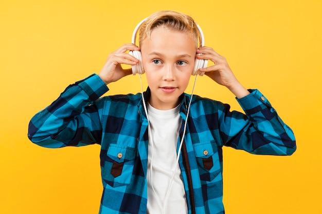 Vista frontal menino colocando fones de ouvido
