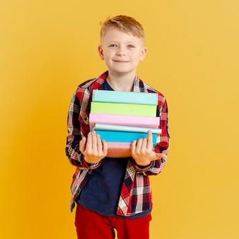 Vista frontal menino com pilha de livros