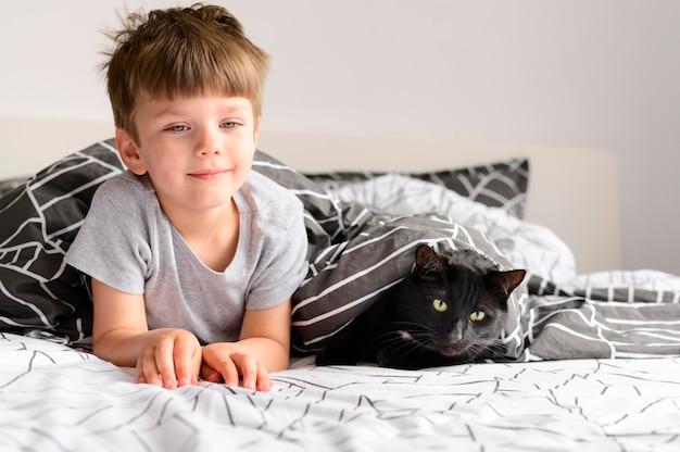 Vista frontal menino com seu gato em casa