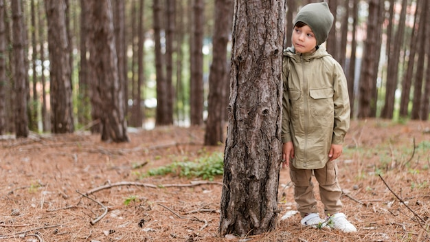 Vista frontal menino de pé ao lado de uma árvore com espaço de cópia