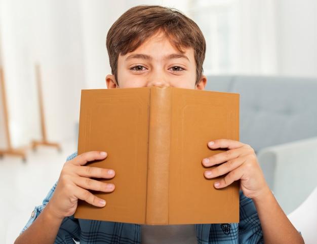Vista frontal menino em casa lendo