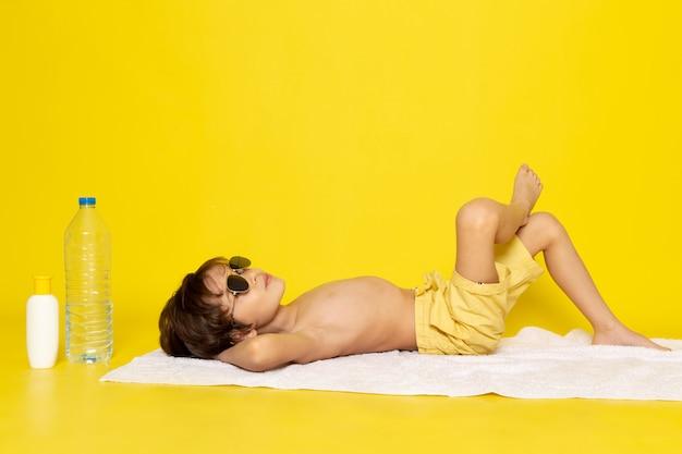 Vista frontal menino em óculos de sol no amarelo