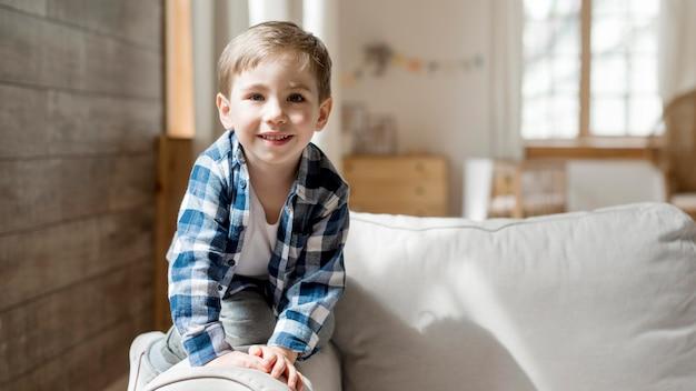 Vista frontal menino feliz em casa jogando