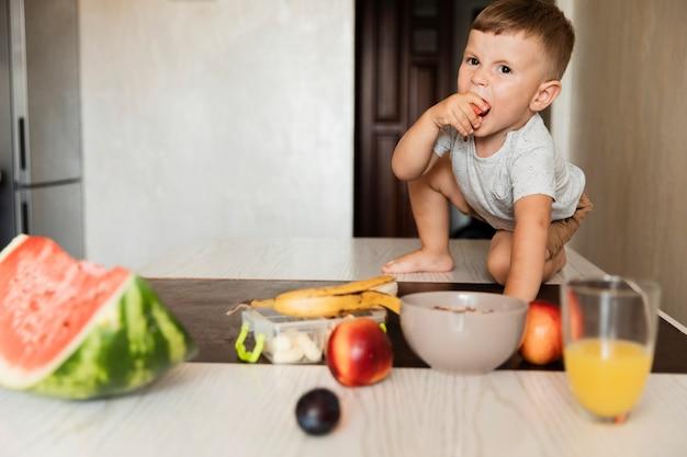 Vista frontal, menino jovem, comer fruta