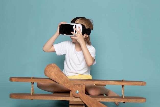 Vista frontal, menino jovem, loiro, cabelos, adorável, doce, bonito, jogando vr, óculos proteção, sobre, azul, fundo