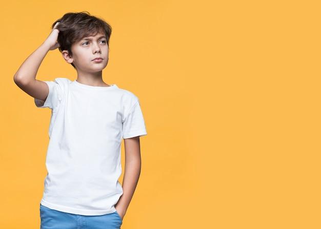 Vista frontal, menino jovem, pensando