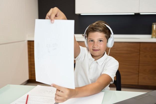 Vista frontal, menino jovem, segurando papel, em casa