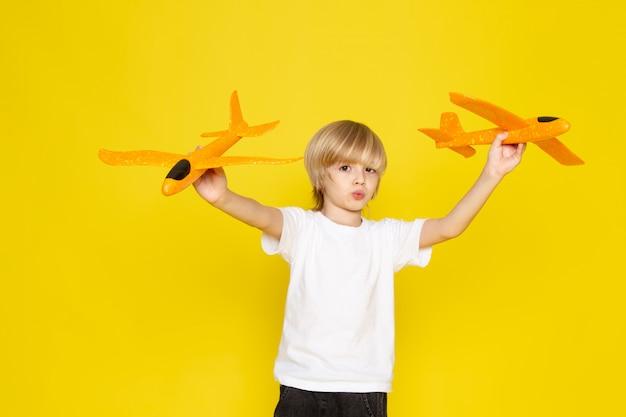 Vista frontal menino loiro de camiseta branca, brincando com aviões de brinquedo laranja no chão amarelo