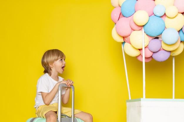 Vista frontal menino loiro de camiseta branca e calção amarelo junto com balões coloridos no amarelo