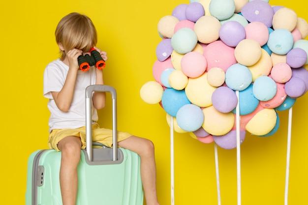 Vista frontal menino loiro de camiseta branca, sentado na bolsa azul junto com balões de ar multicoloridos no chão amarelo