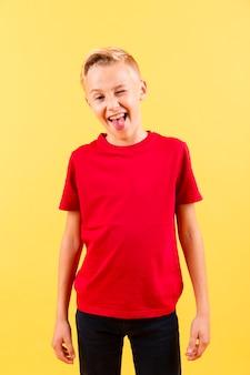 Vista frontal menino piscando e mostrando a língua