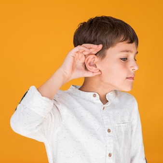 Vista frontal menino tentando ouvir algo