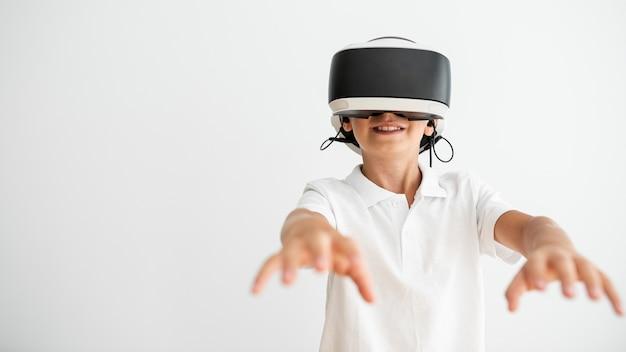 Vista frontal menino usando óculos de realidade virtual