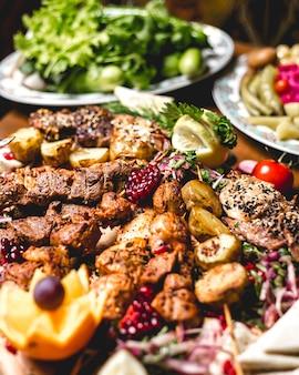 Vista frontal mix kebab no espeto com batatas e rodelas de limão