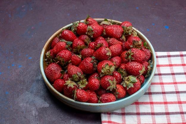 Vista frontal, morangos vermelhos frescos, bagas maduras dentro de uma tigela redonda na superfície escura frutas bagas frescas maduras
