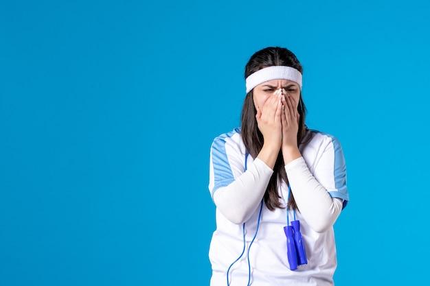 Vista frontal muito feminina com roupas esporte e pular corda no azul