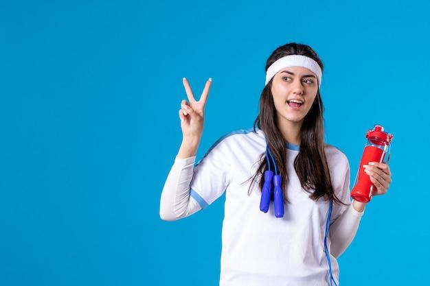 Vista frontal muito feminina em roupas esportivas e pular corda