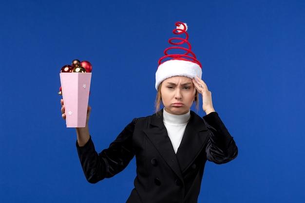 Vista frontal, muito feminina, segurando, árvore, brinquedos, parede azul, ano novo, azul, feriado, mulher