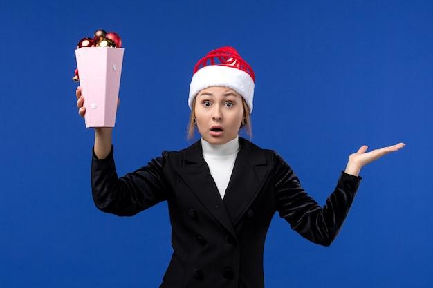 Vista frontal, muito feminina, segurando, árvore, brinquedos, parede azul, ano novo, feriado mulher, azul