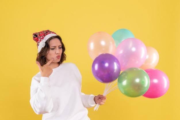 Vista frontal muito feminina segurando balões coloridos em amarelo