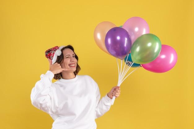 Vista frontal, muito feminina, segurando balões coloridos na mesa amarela, ano novo, emoção, mulher, cor, natal