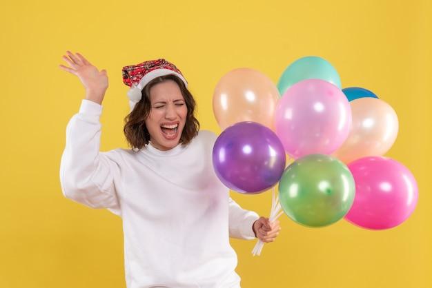 Vista frontal, muito feminina, segurando balões coloridos na mesa amarela, cor natal, ano novo, mulher, emoção