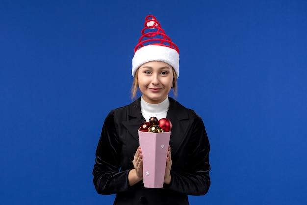 Vista frontal muito feminina segurando brinquedos da árvore de natal na parede azul feriado de ano novo