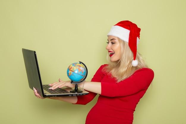 Vista frontal, muito feminina, segurando o pequeno globo terrestre e o laptop na parede verde cor do natal neve ano novo emoção