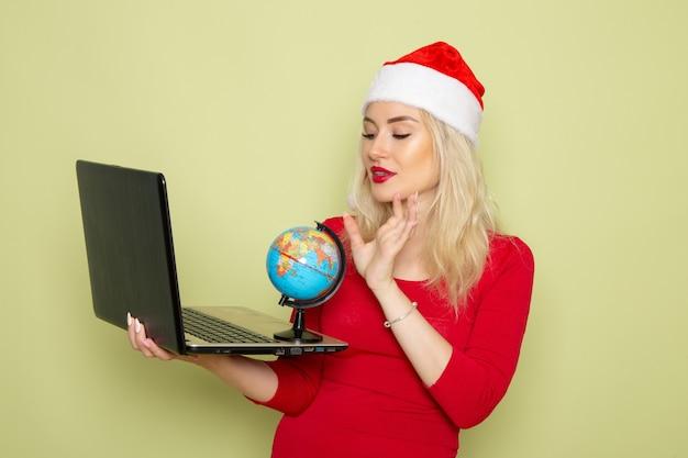Vista frontal, muito feminina, segurando o pequeno globo terrestre e o laptop na parede verde natal neve férias ano novo emoção