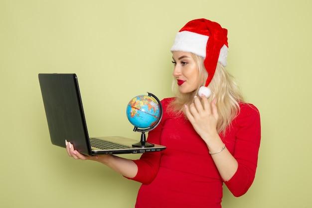 Vista frontal, muito feminina, segurando o pequeno globo terrestre e o laptop na parede verde natal neve férias ano novo emoções
