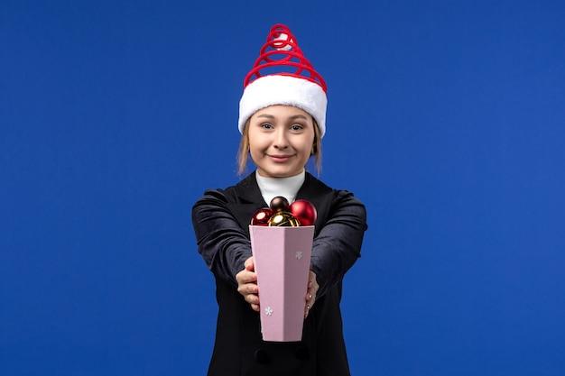Vista frontal, muito feminina, segurando os brinquedos da árvore de natal na parede azul, feriados, ano novo