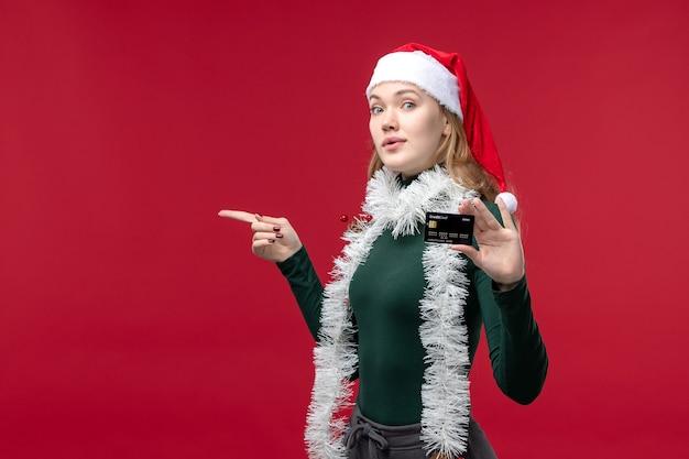 Vista frontal muito feminina segurando um cartão do banco preto sobre fundo vermelho