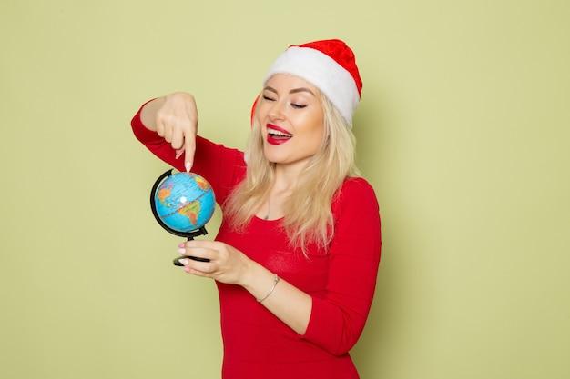 Vista frontal muito feminina segurando um pequeno globo terrestre na parede verde férias natal neve ano novo cor emoção