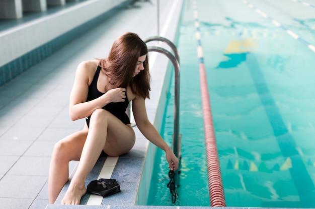 Vista frontal mulher à beira da piscina