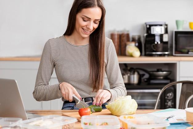Vista frontal mulher a fazer uma pausa para o almoço dentro de casa