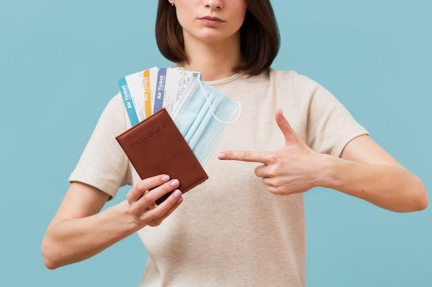 Vista frontal mulher apontando para alguns bilhetes de avião