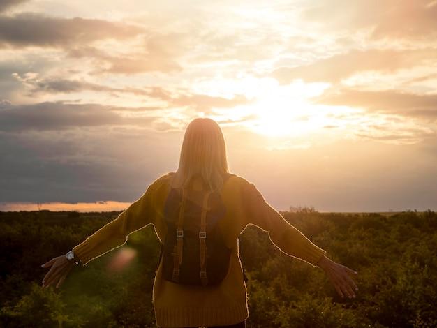 Vista frontal mulher apreciando o pôr do sol