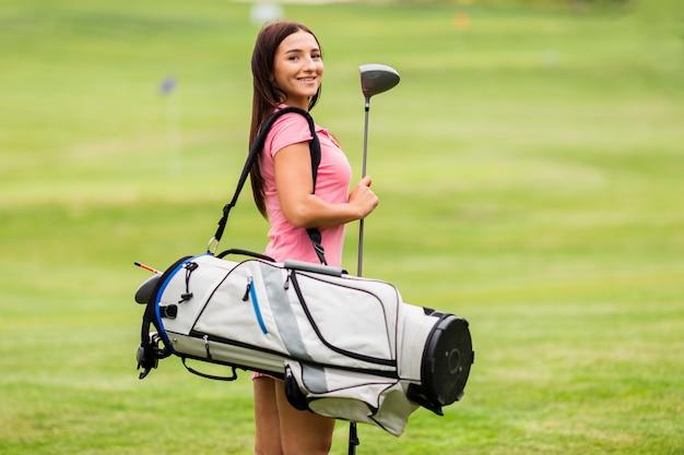 Vista frontal mulher bonita com tacos de golfe