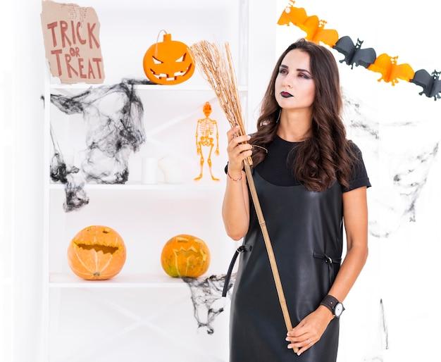 Vista frontal mulher bonita com vassoura de halloween