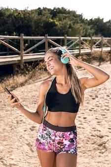 Vista frontal mulher colocando música em seus fones de ouvido