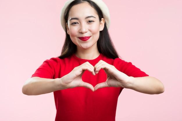 Vista frontal mulher com lábios vermelhos, mostrando a forma do coração com as mãos