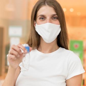 Vista frontal mulher com máscara e desinfetante para as mãos