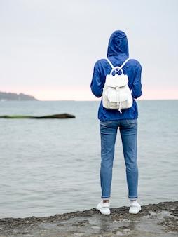 Vista frontal mulher com mochila na beira-mar
