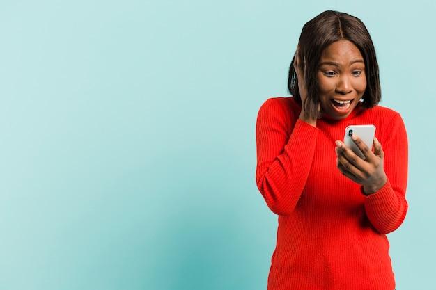 Vista frontal mulher com smartphone em estúdio