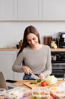 Vista frontal mulher cortando o jantar no trabalho