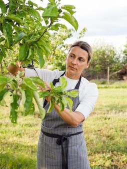 Vista frontal mulher cuidando de uma árvore